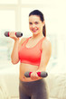 smiling teenage girl exercising with dumbbells