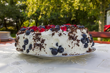 homemade cake topped with blueberries and pieces of red jelly