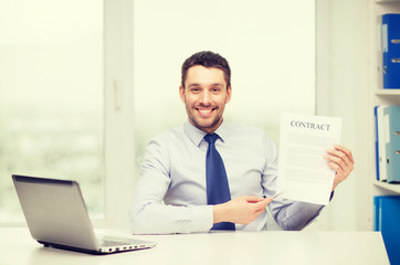businessman with laptop and contract at office