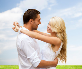 happy couple hugging over natural background