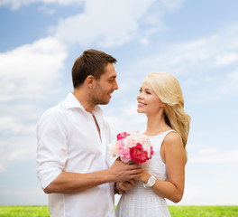 happy couple with flowers over natural background