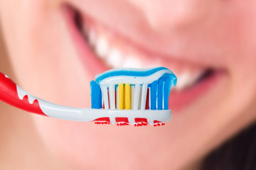 Red toothbrush with blue two color toothpaste on human smile bac