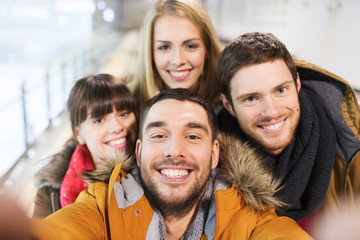 happy friends taking selfie on skating rink
