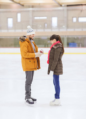happy couple with engagement ring on skating rink
