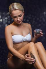 beautiful woman applying therapeutic mud in spa