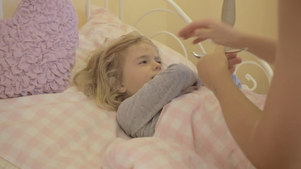 Little girl sick in bed rejecting medicine close up
