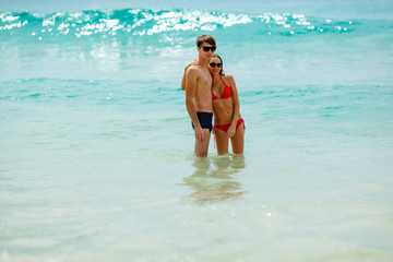 happy couple wearing sunglasses in seawater