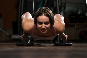 Young Woman Exercising Push Ups On Floor