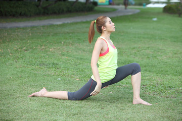 Cute young woman doing physical exercises on lawn