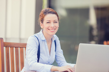 happy smiling woman working on computer laptop outside
