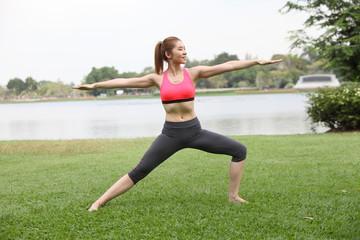 Yoga virabhadrasana II warrior pose by woman on lawn,right side