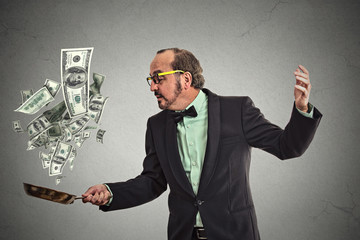 Middle age businessman juggling money dollar bills