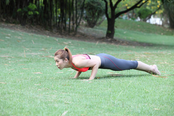 Fitness woman doing push-ups during outdoor cross training worko