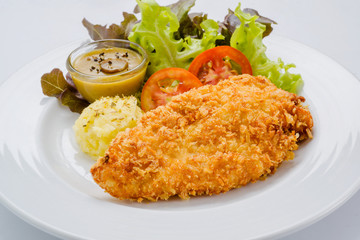 Breaded chicken with mashed potatoes and salad on a white backgr