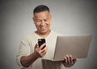 happy surprised man reading news on smart phone holding laptop