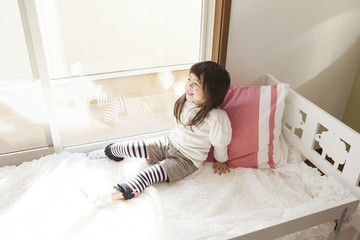 ベッドで寝転ぶ女の子