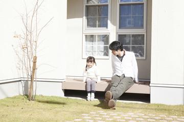 庭で座る親子