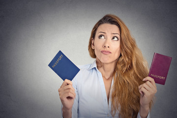 woman holding two passports confused face expression