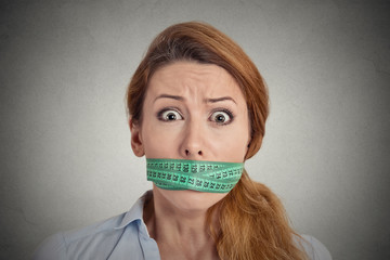 unhappy young woman with measuring tape covering mouth