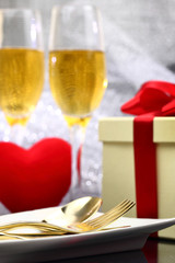 Festive table set with champagne, heart and gift box