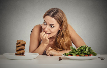 woman deciding to eat healthy food or sweet cookies she craving