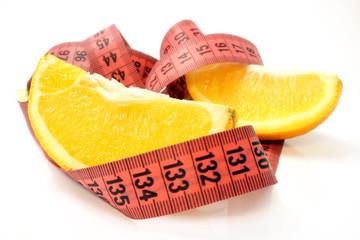 Orange slices with tape measure. Fruit diet.