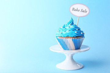 Delicious cupcake with inscription on blue background
