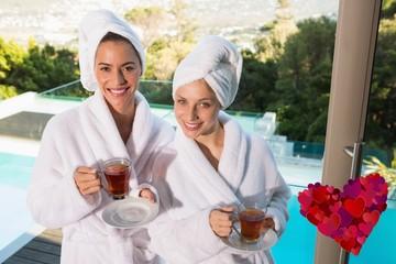 Composite image of smiling women in bathrobes having tea