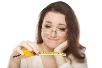 A young woman is pensive at the size shown on the measuring tape