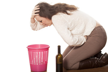 young woman vomits on the trash can
