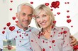 Smiling mature couple sitting on sofa with ar