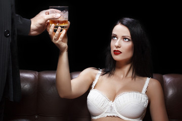 Man gives alcohol to sexy woman