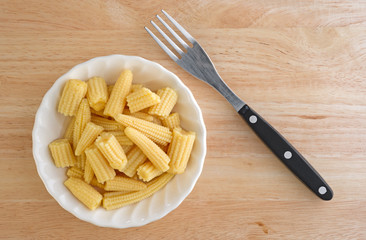 Corn nuggets in white bowl with fork on a wood table