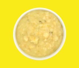 Bowl of potato leek soup on a yellow background