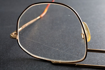 Scratched plastic eyeglasses on a dark background