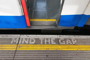 Mind the gap sign with open train door