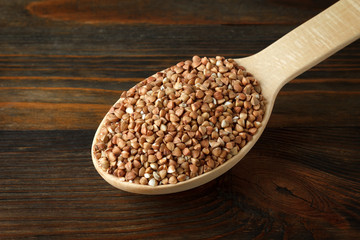 Buckwheat in a wooden spoon on wood
