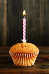 Cupcake with candle on wood