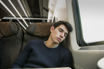 Young man sleeping while traveling on a train sitting in