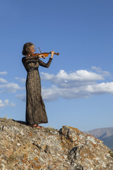 Girl in concert dress, playing the violin, standing on top of a