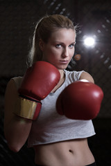 Athletic girl wearing boxing gloves