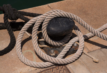 Rusty mooring plate knob and ropes