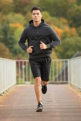 Junger Mann joggt über Brücke