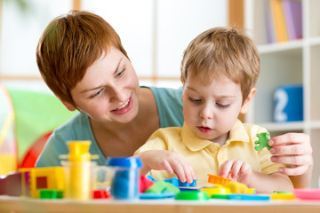 child boy and mother playing colorful clay toy