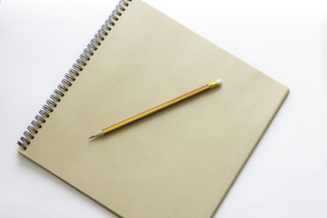 brown notebook and pencil