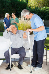 Male And Female Caretakers Helping Senior People