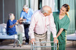 Leinwanddruck Bild - Happy Caretaker Assisting Senior Man In Using Zimmer Frame