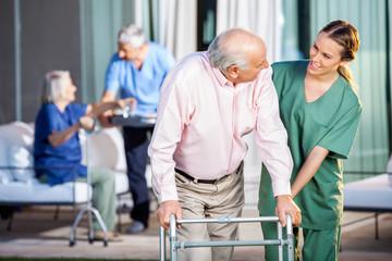 Happy Caretaker Assisting Senior Man In Using Zimmer Frame
