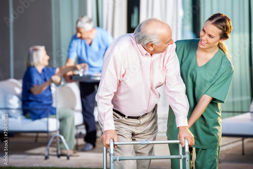 Leinwanddruck Bild Happy Caretaker Assisting Senior Man In Using Zimmer Frame