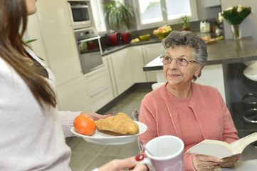 Home helper serving breakfast to elderly woman